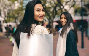 Rear view of two asian women walking in street for shopping. Smiling women out in the city street for shopping.