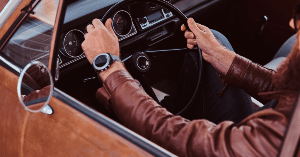 bearded man in leather and sunglasses driving a car very cool